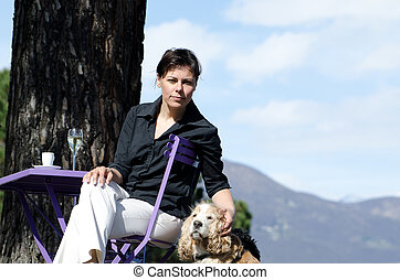 Woman taking a coffee in a patio with her dog