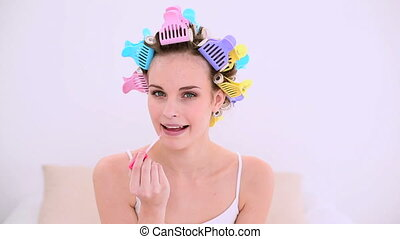 Young model in hair rollers putting on lip gloss at home in...