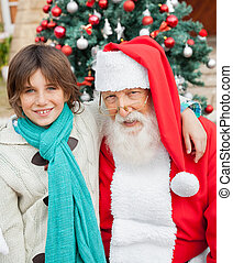 Happy Boy With Arm Around Santa Claus - Portrait of happy...