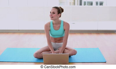 Fit model sitting on exercise mat using her laptop in a...