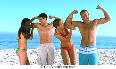 Women feeling biceps of muscled men on the beach in slow...