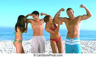 Women feeling biceps of muscled men on the beach in slow...