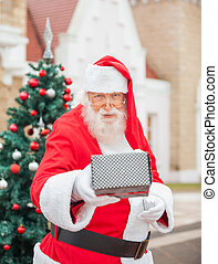 Santa Claus Giving Gift Against House - Portrait of senior...