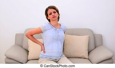 Pregnant woman rubbing her painful back on the couch at home...