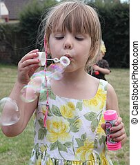 Blowing bubbles - A Young English girl blowing bubbles