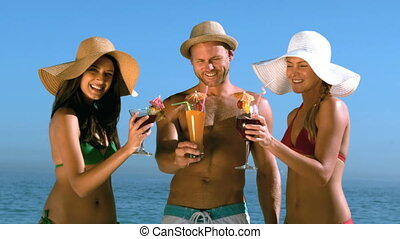 Friends with straw hat clinking cocktails - Friends with...