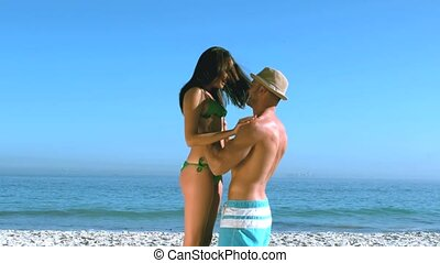 Handsome man lifting up his girlfriend on the beach in slow...
