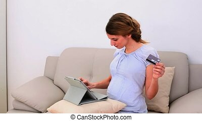 Pregnant woman shopping online with her tablet pc on the...