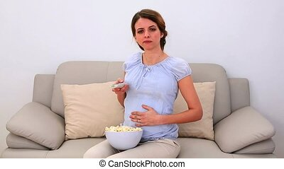 Pregnant woman watching tv and eating popcorn on the sofa at...