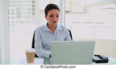 Exhausted businesswoman falling asleep at her desk in her...