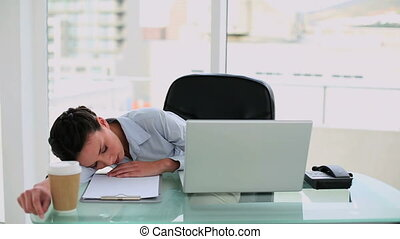 Exhausted businesswoman waking up from a nap at her desk in...
