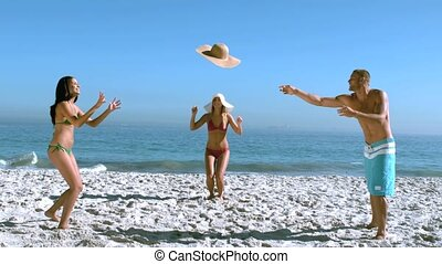 Handsome man throwing friends hat like a frisbee in slow...