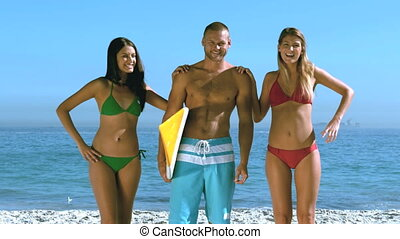 Attractive girls leaning on man at beach
