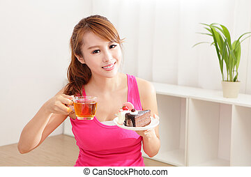 Young woman with a cake and tea - Young beautiful woman with...