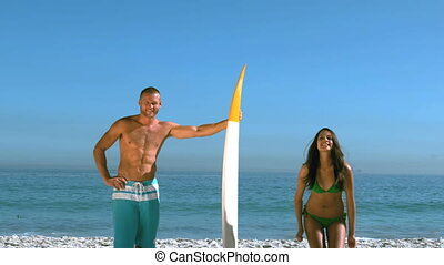 Attractive girl jumping next to a friend with a surfboard in...