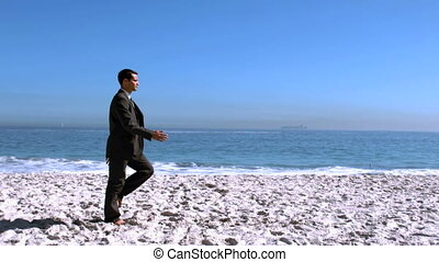 Businessman walking on the beach like a robot in slow motion