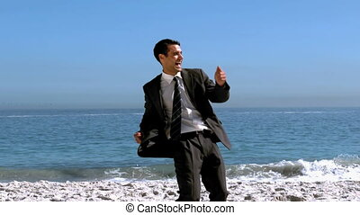 Cheerful free businessman dancing on the beach in slow...