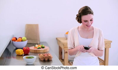 Pretty model phoning in kitchen - Pretty model standing in...