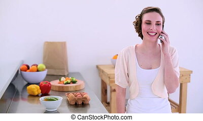 Pretty model phoning in kitchen