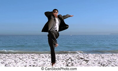 Handsome businessman jumping and kicking on the beach in...
