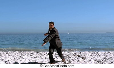 Businessman jumping and kicking on the beach in slow motion