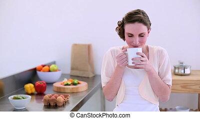 Pretty model drinking in kitchen - Pretty model standing in...