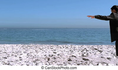 Businessman doing acrobatics on the beach in slow motion