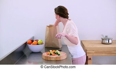 Pretty model standing in kitchen taking peppers from grocery...