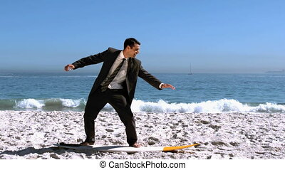 Businessman balancing on surfboard on the beach in slow...