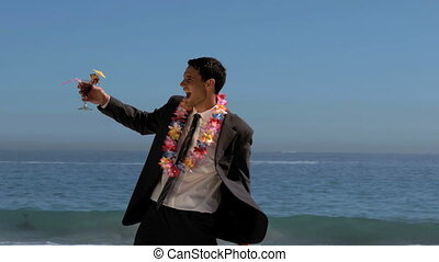 Attractive businessman dancing on the beach while he is...