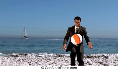 Attractive businessman playing with beachball in slow motion