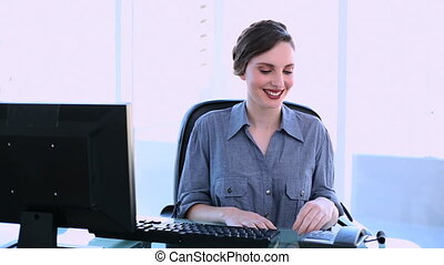 Pretty businesswoman answering phone at her desk in office