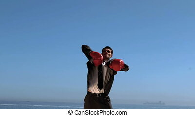 Attractive businessman jumping with red boxing gloves in...