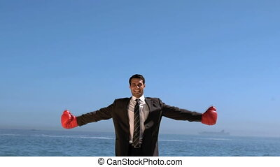Businessman on the beach raising arms in slow motion