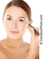 Woman holding a tiny cosmetic brush - Beautiful young woman...