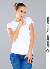 Playful young woman asking for secrecy or quiet smiling at...