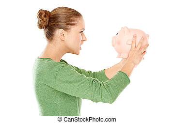 Angry woman arguing with her piggy bank in desperation that...