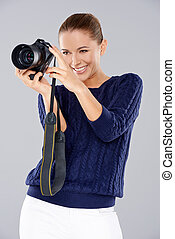 Happy woman holding a professional camera smiling as she...