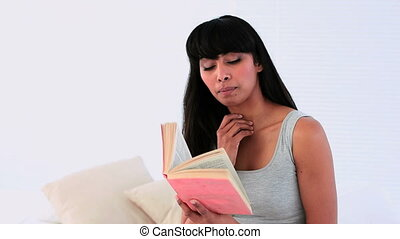 Attractive woman reading a book on her bed at home in...