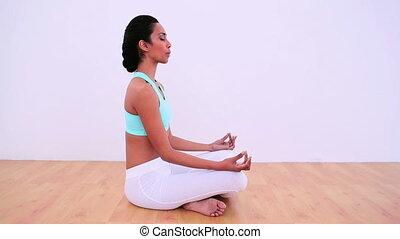 Peaceful woman meditating in lotus