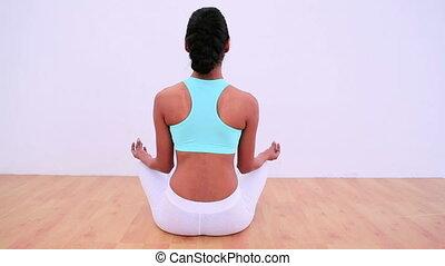 Fit woman meditating in lotus posit