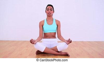 Calm woman meditating in lotus posi