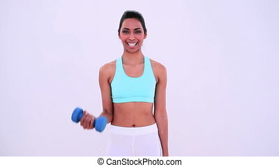 Fit woman lifting hand weights and smiling at camera
