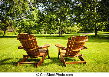 Summer relaxing - Two wooden adirondack chairs on lush green...
