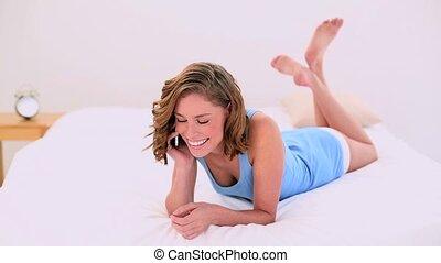 Joyful woman lying on her bed