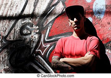 Rapper leaning on a Wall - A young Rapper leaning against a...