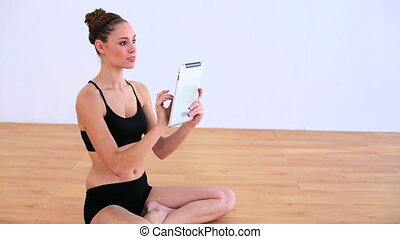 Concentrated woman using a tablet - Concentrated brunette in...