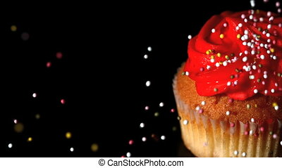 Sprinkles falling onto a cupcake