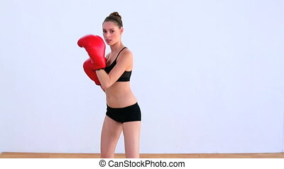 Dynamic woman boxing with red glove