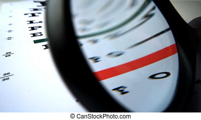 Close up of a magnifying glass falling on an eye test in...